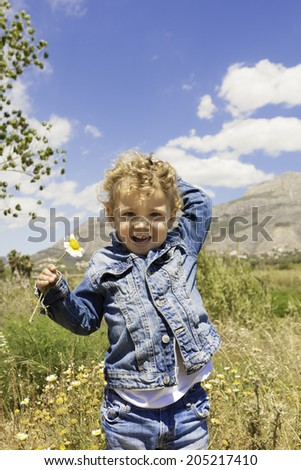 child smiling with flower in the field standing - stock photo