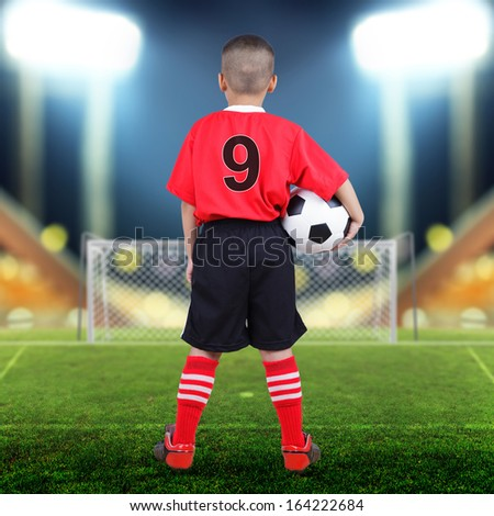 Child soccer player on soccer field with bright spotlights - stock photo