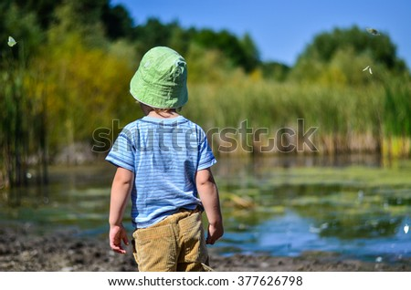 child standing back looking at the lake. Sideways fly butterfly - stock photo