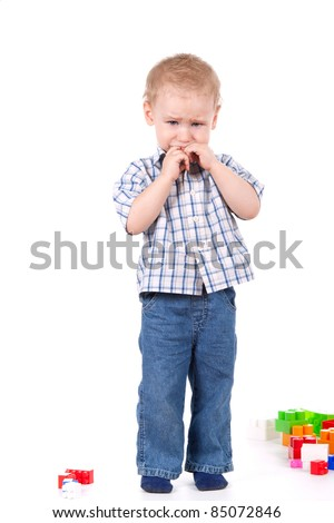 child standing crying, near toys over white background - stock photo
