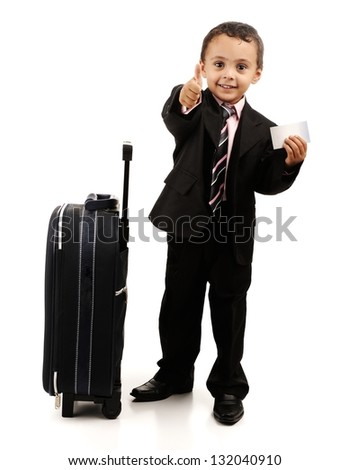 Child standing near luggage, holding postcard with finger up - stock photo