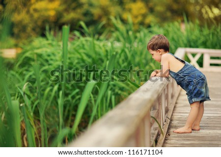 child standing near the rails on the river - stock photo