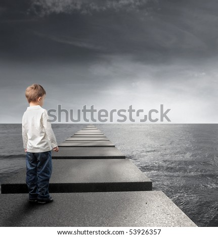 Child standing on a pad and observing the sea on the background - stock photo