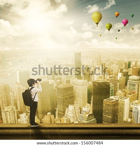 Child standing on the top of a skyscraper and looking at hot balloons - stock photo