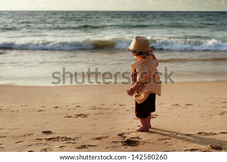 Child stands on the beach by the sea and watching the sea
