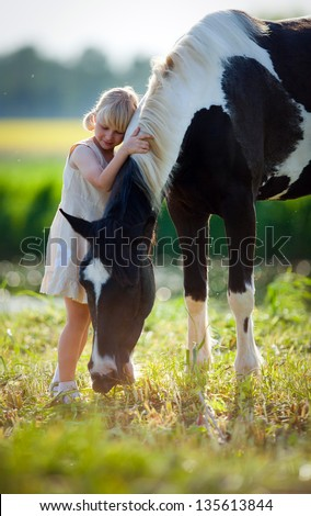 Child stands with a horse in the field. - stock photo
