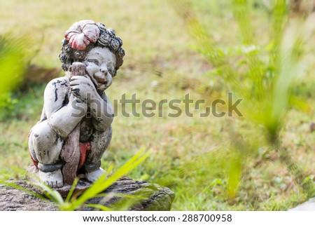 Child statue in the garden - stock photo