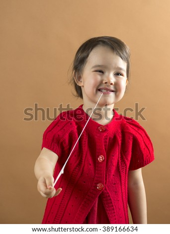 Child stretching a chewing gum from her mouth - stock photo