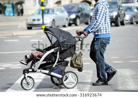 Child stroller and man on zebra crossing - stock photo