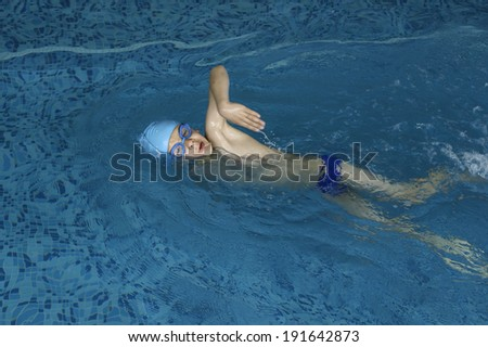 Child swimmer in swimming pool. Blue color swimming pool