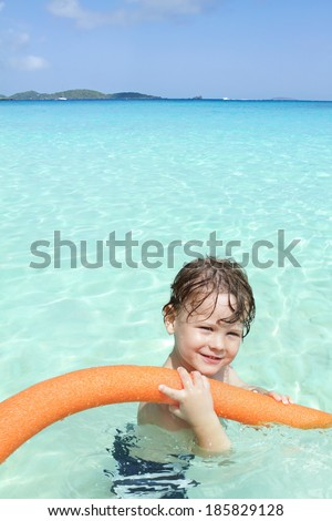 Child swimming in clear waters of a tropical ocean, smiling and looking at the camera