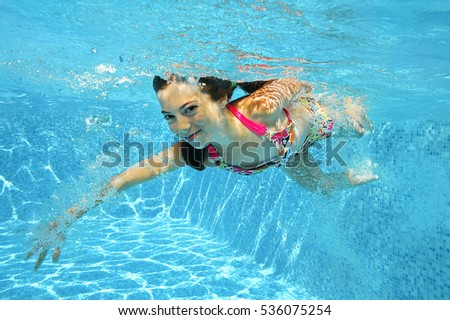 Child swims in pool underwater, girl has fun under water, active kid fitness sport on family vacation