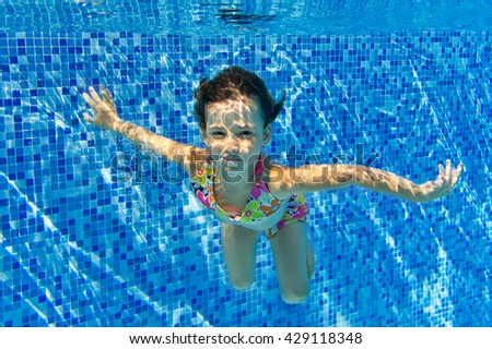 Child swims in pool underwater, happy active girl has fun under water, kid sport on family vacation  - stock photo