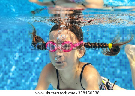 Child swims in pool underwater, happy active girl in goggles has fun in water, kid sport on family vacation