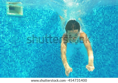 Child swims in pool underwater, happy active girl jumps, dives and has fun, kid sport on family vacation  - stock photo