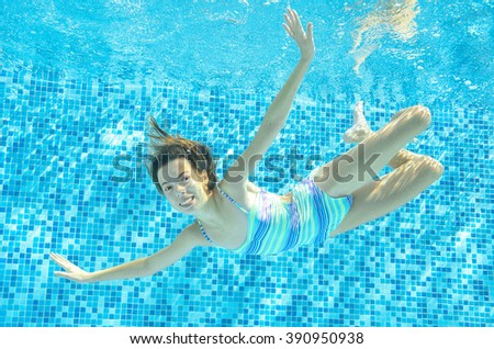 Child swims in pool underwater, happy active girl jumps, dives and has fun under water, kid sport on family vacation  - stock photo