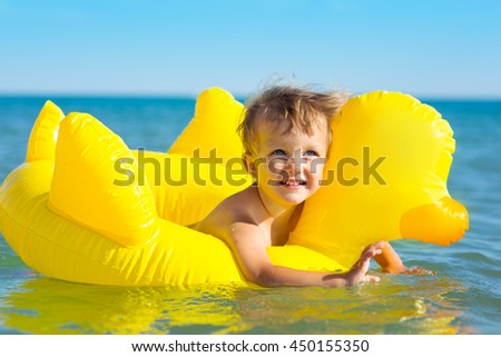 Child swims in the sea in inflatable ring
