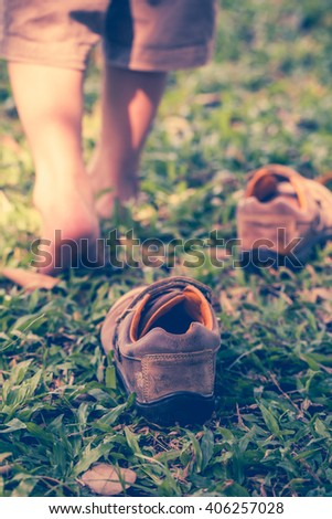 Child take off leather shoes. Close up child's foot learns to walk on grass, reflexology massage. Kid relax in garden. Shallow depth of field (dof), selective focus. Retro style. - stock photo