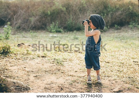 Child taking a picture in the forest - stock photo