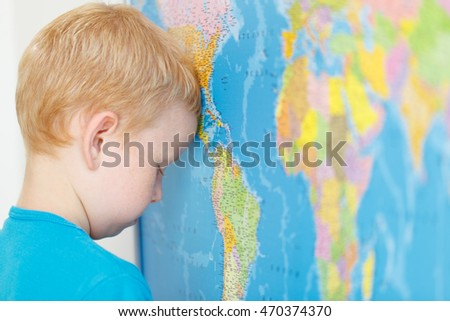 Child think about the world near the map