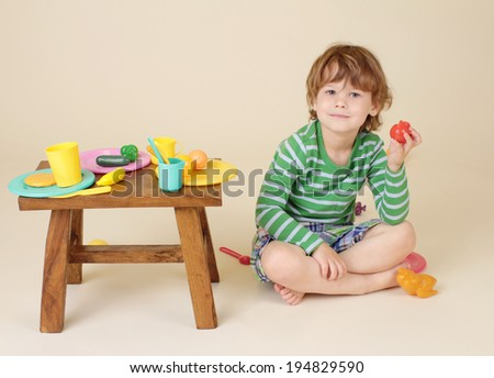 Child, toddler boy, eating and playing with pretend food - stock photo