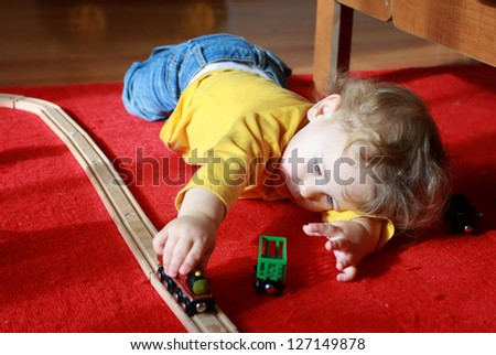Child, toddler boy, playing at home with trains and tracks - stock photo