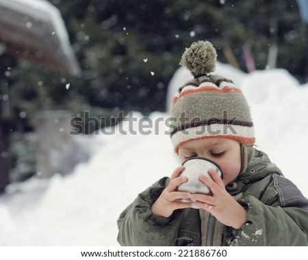 Child toddler in snow, in winter drinking a hot drink.  - stock photo