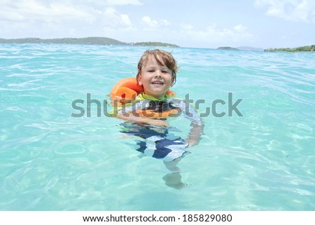 Child, toddler, swimming in a tropical Caribbean ocean, summer vacation - stock photo