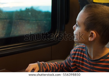 Child traveling on train, looking from a window.