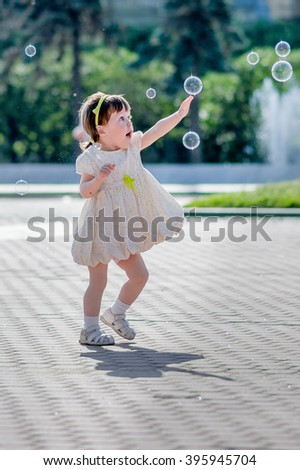 Child trying to catch soap bubble - stock photo