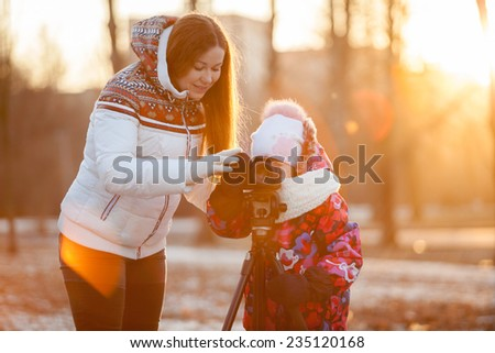 Child under the supervision of mother pushing button of camera mounted on tripod - stock photo