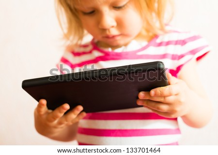 child uses a Tablet PC - stock photo