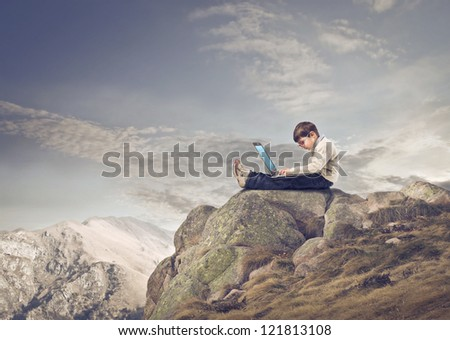 Child using a laptop computer on a mountain