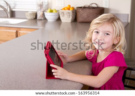 Child using a tablet computer sitting in kitchen at home - stock photo