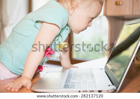 Child using laptop at home. Little girl play some computer game or watching a cartoons