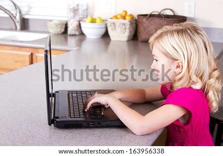 Child using laptop computer sitting in kitchen at home