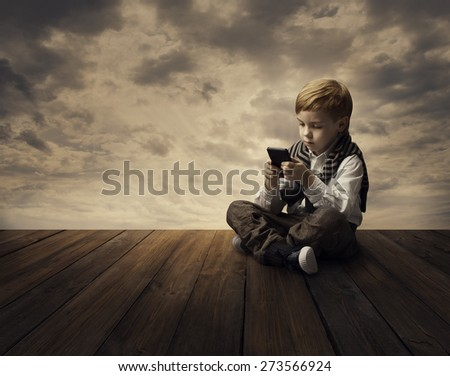 Child Using Mobile Phone, Little Kid Boy Playing Cellular Smart Telephone in Hand - stock photo