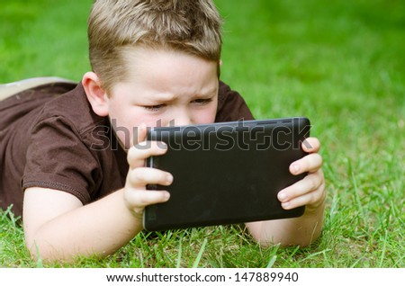 Child using tablet computer outdoors - stock photo