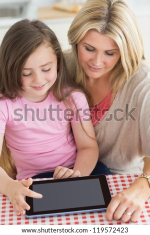 Child using tablet pc with mother at kitchen table