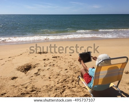 Child using white tablet pc on sunny beach outdoors background. Mobile photography design idea