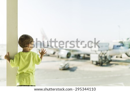 Child waiting for his plane at the airport of Barcelona - stock photo