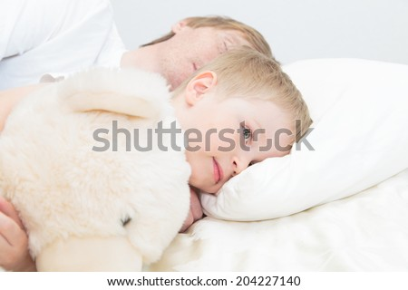 child wake up in early morning while father asleep in bed - stock photo