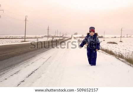 Child walking along the road one winter