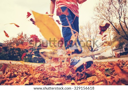 Child walking and kicking fall leaves. Focus on jeans and background leaves. Motion blur. Instagram effect. - stock photo