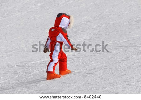 Child walking and playing on a snow slope