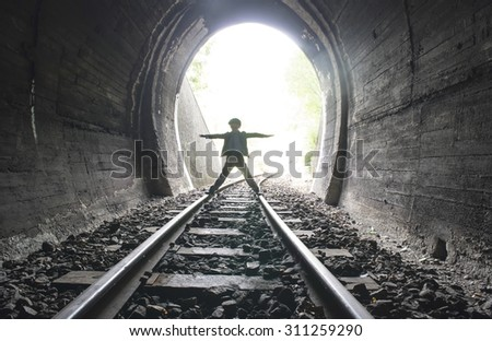Child walking in railway tunnel. Vintage clothes - stock photo
