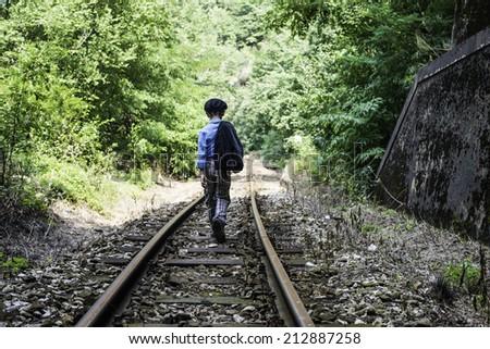 Child walking on railway - stock photo