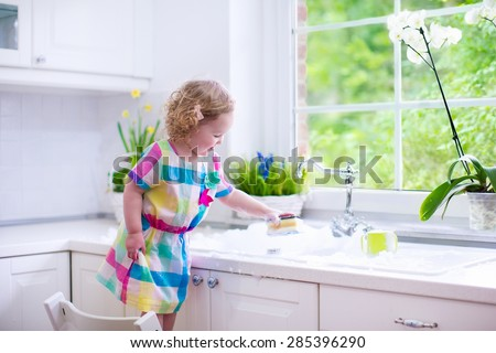 Child washing dishes. Kids wash plates and cups. Little girl helping in the kitchen playing with water and foam in a white sink with retro tap. Chores for children. Modern home interior with window. - stock photo