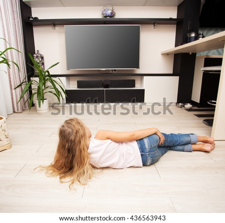 Child watching TV at home. Girl looking at television