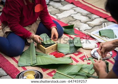 Child wear traditional dress Ao Dai learning to make Chung cake by hands closeup, Chung cake is the most important traditional Vietnamese lunar New Year (Tet) food.
